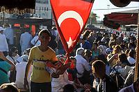 TURKEY Istanbul people eat fish bread rolls at Golden Horn, turkish flag / TUERKEI Istanbul, Menschen essen Fischbroetchen am Goldenen Horn, tuerkische Flagge