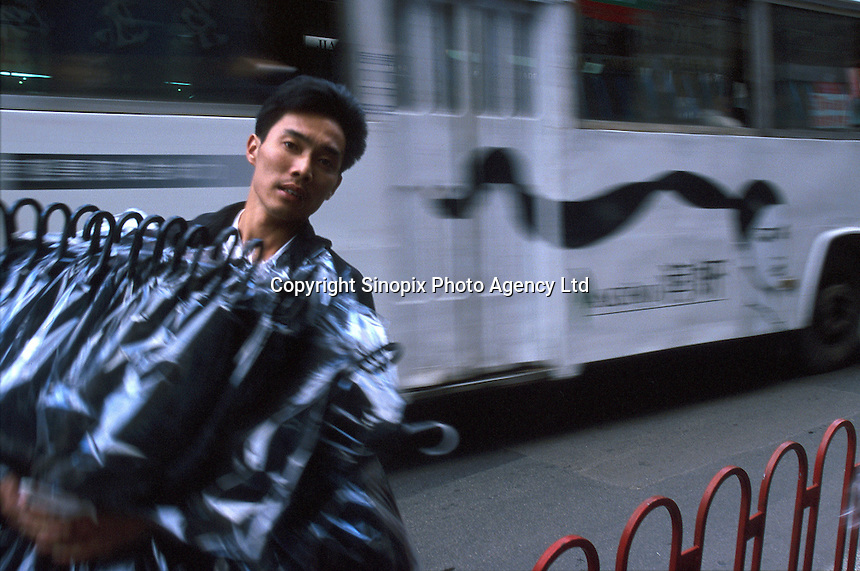 A man transports suits on a street in Shanghai, China..08-APR-01
