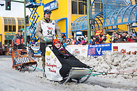 Ray Redington Jr and team leave the ceremonial start line with an Iditarider at 4th Avenue and D street in downtown Anchorage, Alaska during the 2015 Iditarod race. Photo by Jim Kohl/IditarodPhotos.com