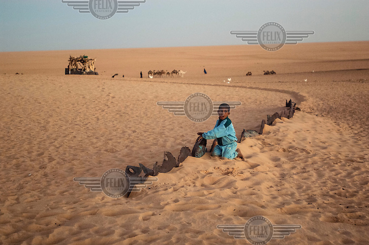 A boy sits next to boundary markers in the sand in the Sahara Desert town of Boujbeja. /Felix Features