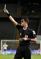 BOGOTA - COLOMBIA - 18 – 11 - 2017: Alexander Ospina (Izq.),  arbitro, muestra tarjeta amarilla a Kevin Balanta Lucumi (fuera de Cuadro) jugador de Deportivo Cali, durante partido de la fecha 20 entre Millonarios y Deportivo Cali, por la Liga Aguila II-2017, jugado en el estadio Nemesio Camacho El Campin de la ciudad de Bogota. / Alexander Ospina (L), referee, shows yellow card to Kevin Balanta Lucumi (Out of Frame), player of Deportivo Cali, during a match of the date 20th between Millonarios and Deportivo Cali, for the Liga Aguila II-2017 played at the Nemesio Camacho El Campin Stadium in Bogota city, Photo: VizzorImage / Luis Ramirez / Staff.