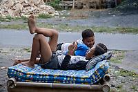 Yogyakarta, Java, Indonesia.  Village Boys Playing with Cell Phones.