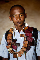 A member of a Muslim 'self-defence' group draped with 'Gris Gris' amulets that confer good fortune and protection on their wearers. They are animist in origin but also worn by both Muslims and Christians throughout west and central Africa. In late 2012 after years of instability and conflict, the Seleka, a predominantly Muslim rebel group, fuelled by grievances against the government, overran the country and, In March 2013, ousted President Francois Bozize, who fled the country. The rebel's leader Michel Djotodia was proclaimed president in August 2013. He disbanded the Seleka in September 2013 but law and order collapsed and ex-Seleka fighters roamed the country committing atrocities against the civilian population. In an attempt to defend their lives and property vigilante groups, calling themselves Anti-Balaka (Anti-Machete), formed to confront the ex-Seleka fighters but soon began to take reprisals against the wider Muslim population and the conflict became increasingly sectarian. By December 2013, with international fears of a genocide being voiced, French led peacekeepers deployed to the country began to act on a UN mandate to disarm the fighters and protect the civilian population. However, they have struggled to contain the situation. Much of the Muslim population, in particular, have been forced into ghettos where they are suffering from food shortages and limited access to healthcare. Often, only a few peacekeepers stand between them and a massacre by vengeful Anti-Balaka militants. UN reports describe 'thousands' killed, while over 600,000 people have been internally displaced and a further 200,000 have fled the county.