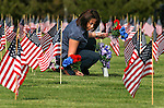Sonya Vasquez places flowers on the graves of family members who were veterans at the Lone Mountain Cemetery in Carson City, Nev., on Friday, May 25, 2012. Volunteers from the D.A.V., American Legion, Carson High School ROTC and Boy Scout Troop 145 placed more than 1,400 flags on the graves of veterans in honor of Memorial Day..Photo by Cathleen Allison