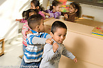 Education preschool 2-3 year olds horizontal group of children walking in connected line (human train)