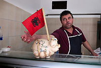 """Albania. Tirana. A butcher in his shop. On the counter, a piggy bank with the written words """" My first bank"""" and the Albanian flag. The flag of Albania is a red flag with a silhouetted black double-headed eagle in the center. The red stands for bravery, strength and valor, while the double-headed eagle represents the sovereign state of Albania. The flag was first adopted as the national flag of modern Albania in 1912. Tirana is the capital and most populous city of the Republic of Albania. The city is also the capital of the surrounding county of Tirana, one of 12 constituent counties of the country. 20.5.2018 © 2018 Didier Ruef"""