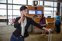Attractive young female businesswoman holds conversation on cell phone at a airport gate departure lounge in the Austin–Bergstrom International Airport (ABIA).