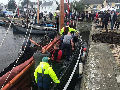 Dangerously sociable for pandemic times – communal unloading of the turf at Kinvara after it has been raced in time-honoured style across Galway Bay from Connemara