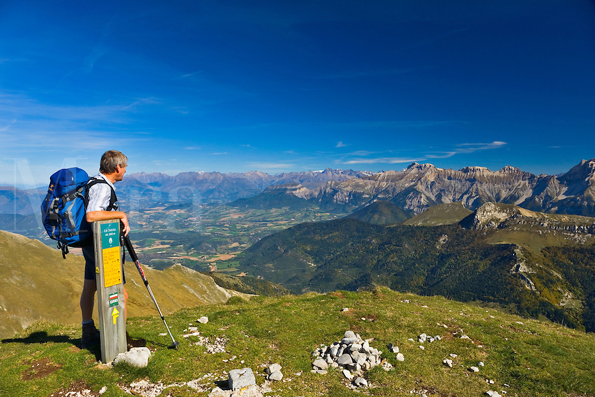 Walker relaxes on the summit of Mt. Jocou and enjoys the view over the Valley du Drac, Isere and the Alpine peaks. Diois. Drome. France.