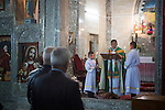 16/11/14. Alqosh, Iraq. Milad (left) holds and candle a Sunday service for orphans and residents of Alqosh in the monastery's Der Saida Church.