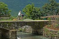 European woman riding her bike over a bridge, Yangshuo, Guangxi, China.