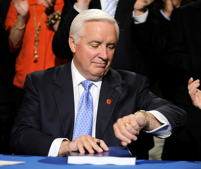 Pennsylvania Gov. Tom Corbett checks his watch following his signing the state budget documents in the rotunda of the capitol Thursday, June 30, 2011 in Harrisburg, PA. Corbett promised an on time budget with no new taxes as a campaign promise. (AP Photo/Bradley C Bower)