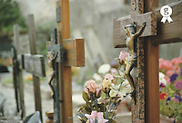 Flowers beside grave with Crucifix in cemetery, close-up (Licence this image exclusively with Getty: http://www.gettyimages.com/detail/200388010-001 )