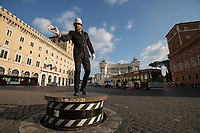 """Rome, Italy. 26th Mar, 2021. Documenting the return of the """"Vigile"""", the Traffic Officer, member of the Rome Municipal Police Force (1.), directing the traffic from his historic and iconic pedestal in Piazza Venezia (2.), definitely one of the most chaotic and famous landmark of the Eternal City. <br /> The elegant Vigile portrayed in these photos is the veteran traffic officer, Pierluigi Marchionne, whose moves recall a Conductor of an Orchestra, a Dancer, an Actor. In fact, he was chosen to be the Vigile in Piazza Venezia in the 2012 Woody Allen's film """"To Rome With Love"""" (3.). Surely, the Traffic Officer in Piazza Venezia reminds the famous and unforgotten Roman actor, Alberto Sordi, in the 1960 classic Luigi Zampa's film """"Il Vigile"""" (4.).<br /> <br /> Footnotes & Links:<br /> 1. https://www.comune.roma.it/web/it/corpo-di-polizia-locale-di-roma-capitale.page<br /> 2. https://en.wikipedia.org/wiki/Piazza_Venezia<br /> 3. https://en.wikipedia.org/wiki/To_Rome_with_Love_(film)<br /> 4. https://en.wikipedia.org/wiki/The_Traffic_Policeman & https://youtu.be/H3WiIrOqkBM<br /> Return of Traffic Cops to Landmark Piazza Brings Unlikely Joy in Rome (Source, Nytimes.com, 20th Mar, 2021) https://www.nytimes.com/2021/03/20/world/europe/rome-coronavirus-traffic-officers.html"""
