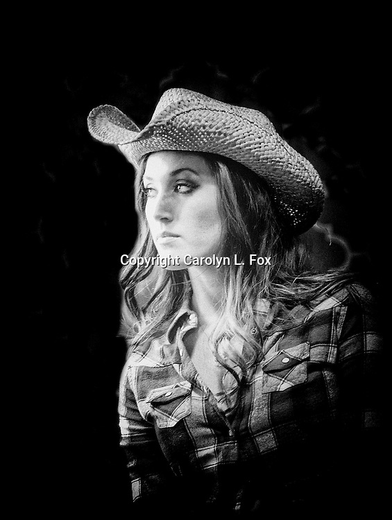 A cowgirl, wearing a western hat, is set off against a black background.