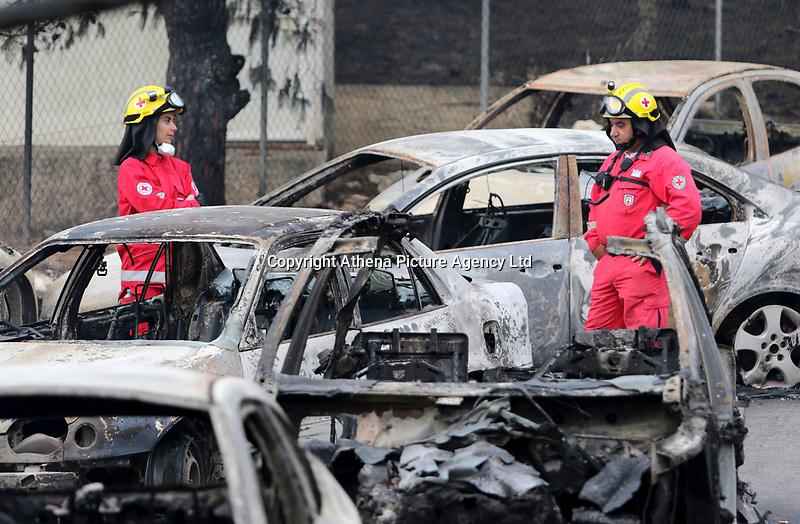 Pictured: Firemen search through rows of burned cars in the Mati area, Kokkino Limanaki near Rafina, Greece. Tuesday 24 July 2018<br /> Re: Deaths caused by wild forest fires throughout Greece.