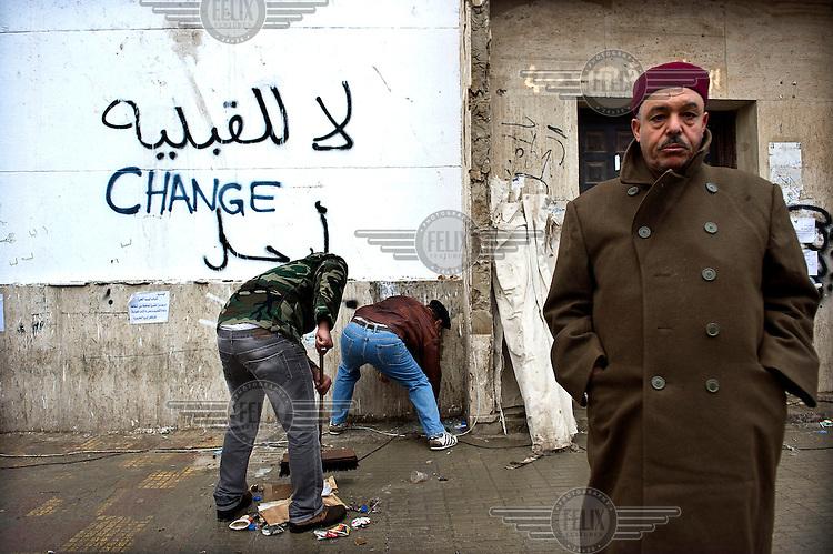 Residents of Benghazi sweeping the streets after days of fighting between pro and anti government forces in Benghazi. A wall shows a graffiti in Arabic and English which reads: 'Change'. The eastern city of Benghazi, birthplace and stronghold of the revolution against the regime of Muammar Gaddafi, was taken by rebel forces after heavy fighting with forces loyal to the regime. ....foto: Sven Torfinn. Libya, Benghazi, Februari 2011. Bewoners van Benghazi hebben zich georganiseerd. 13 comitees zijn aangesteld om er voor te zorgen dat zaken als stroom, water, reiniging, gezondheidszorg blijven funcitoneren nu Benghazi niet meer onder het gezag van de regering Khaddafi valt. Teams van vrijwilligers vegen de straten schoon.