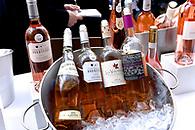 Still life photo of bottles of rosé wines on ice.
