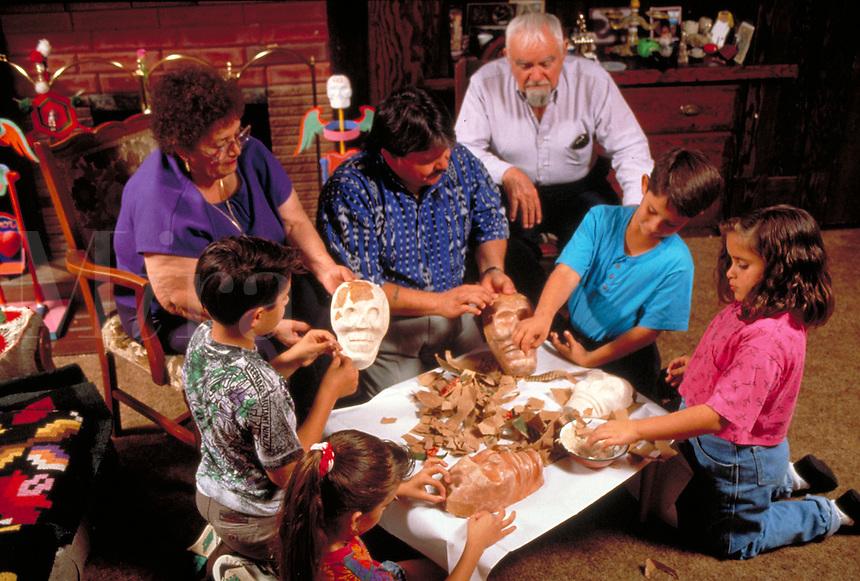 HISPANIC FAMILY AT HOME MAKING PAPIER MACHE MASKS OF SKULLS FOR DAY OF THE DEAD CELEBRATION. HISPANIC FAMILY. SACRAMENTO CALIFORNIA.