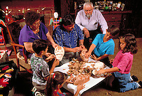HISPANIC FAMILY AT HOME MAKING PAPIER MACHE MASKS OF SKULLS FOR DAY OF THE DEAD CELEBRATION. HISPANIC FAMILY. SACRAMENTO CALIFORNIA.