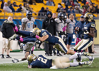 Pitt defensive players K'Waun Williams (2) and Anthony Gonzalez (28) upend Old Dominion ball carrier Antonio Vaughan. The Pitt Panthers defeated the Old Dominion Monarchs 35-24 at Heinz Field, Pittsburgh, Pennsylvania on October 19, 2013.
