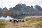 Students of the Cape Farewell Youth Expedition, organized by the British Council of Canada, explore the coast of Greenland while the ship waits in the background. The students are exploring the Tasermiut Fjord.
