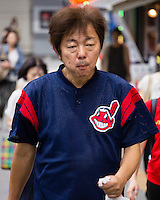 """A Cleveland Indians """"fan"""". He can be a real fan. Or he could bought this t-shirt in a bargain shop. There are many shops in Japan that sell goods with American stores and teams logos. """"Whole Foods"""", for example, is popular in Harajuku."""