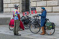 """Ein Coronaleugner und Impfgegner steht am Internationalen Holocaustgedenktag der Opfer des Nationalsozialismus vor dem Reichstagsgebaeude und redet mit einer Passantin. Er protestiert gegen die Corona-Politik der Bundesregierung mit LED-Schildern auf denen die Hakenkreuzfahne nachempfunden ist und statt dem Hakenkreuz ein Virus-Symbol eingestzt ist. Zusaetzlich steht """"Heil Impfung"""" auf einem Schild.<br /> 27.1.2021, Berlin<br /> Copyright: Christian-Ditsch.de"""