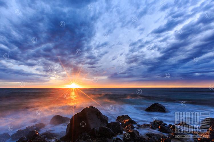 A cloudy day breaks apart with a dramatic sunset at Ke'e Beach, Ha'ena State Park, Na Pali Coast, Kaua'i.