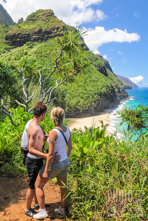 Hikers on the Kalalau Trail enjoy the view of the Na Pali Coast, Kaua'i
