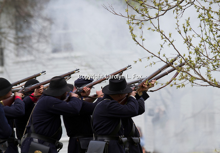 Union soldiers fire their cap and ball muzzle rifles  during a Civil War reenactment.