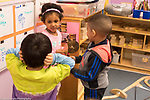 Education Preschool classroom scenes 3-4 year olds boy covering his ears as classmates play with cymbals