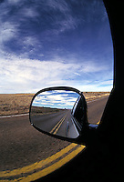Empty road reflected in car's rear view mirror<br />