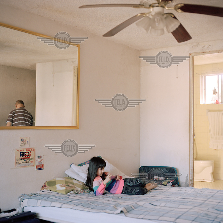 Enrique Contreras' granddaughter rests while he is relected in a mirror in the room where he lives in the northern border city of Nuevo Laredo. He left his native Venezuela and lived in Argentina for six years, but decided, he says, to head for the USA fearing an economic crisis and hoping to meet his wife who already lives there. <br /> Terrified of the organised crime groups operating in the city, who already extorted him, Enrique barely leaves the hotel, spending the days indoors looking after his granddaughter while his son-in-law works. They are waiting for their asylum hearings in the US and say they would like to move to another, safer city in Mexico but is scared to even go to the bus station for fear of being kidnapped, as it's known gangsters prey on families with young children.