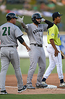 First baseman Francisco Tostado (8) of the Augusta GreenJackets shakes his hips at teammates after hitting a triple in a game against the Columbia Fireflies on Friday, May 31, 2019, at Segra Park in Columbia, South Carolina. The third base coach is Carlos Valderrama and the third baseman is Mark Vientos. Augusta won, 8-6. (Tom Priddy/Four Seam Images)