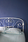 Blue bedroom with white iron bed.