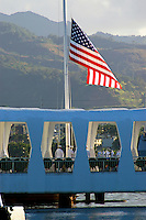 Sailors raise the flag to half-mast on December 7th, 2005.  A US Navy ship lined with sailors is visible in background.