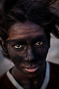 A young miner, Vijay Bhuia poses for a portrait in Bokapahari in Jharia, Jharkhand, India. The miners work for 9-10 hours a day and make Rs.150 ($3.5) a day loading the coal trucks in the BCCL coal mines in Jharia. Coal fires rage just below the surface of the ground, making it too hot to walk with naked feet, noxious gases spew up from fissures, making the environment toxic. Photo: Sanjit Das