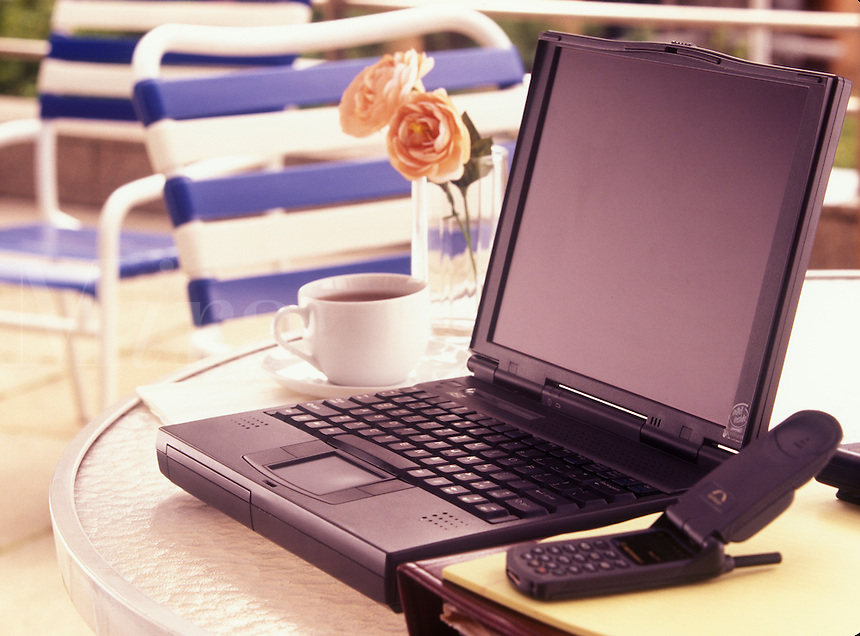 Laptop computer and cell phone on patio table.
