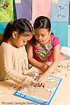 Preschool ages 3-5 older girl visiting classroom doing puzzle with younger child vertical