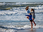 Brother and sisters jumping in surf at the beach.