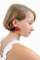 Girl (10) wearing two cherries behind ear (Licence this image exclusively with Getty: http://www.gettyimages.com/detail/103301310 )