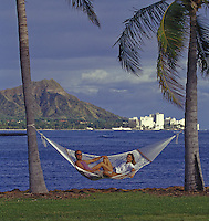 Couple lying in hammock between palm trees, with Waikiki and Diamond Head in background