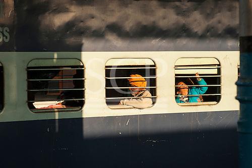 Kalka, Himachal Pradesh, India. passengers on a mainline train through barred windows.