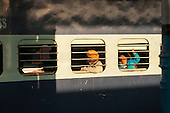 Kalka, Himachal Pradesh, India. passengers on a mainline train through barred windows.