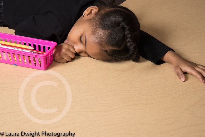 Education Preschool Childcare 3-4 year olds girl tired at start of day resting on table sucking thumb