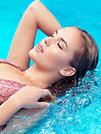 Closeup of beautiful young woman face with closed eyes in blue water Image © MaximImages, License at https://www.maximimages.com