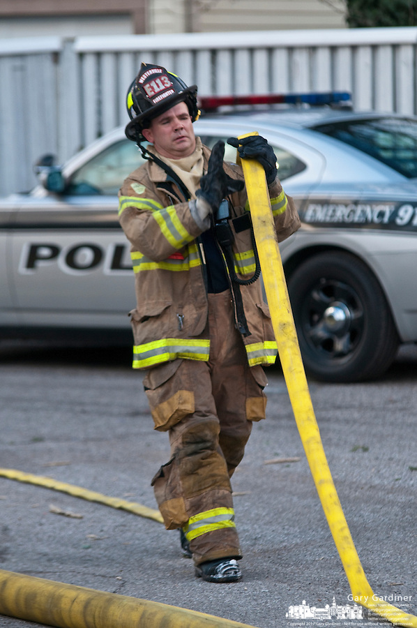 Westerville fire fighters roll up hoses and retrieve fire fighting equipment after fighting a fire in a garage where they extinguished a fire in a Corvette parked there.
