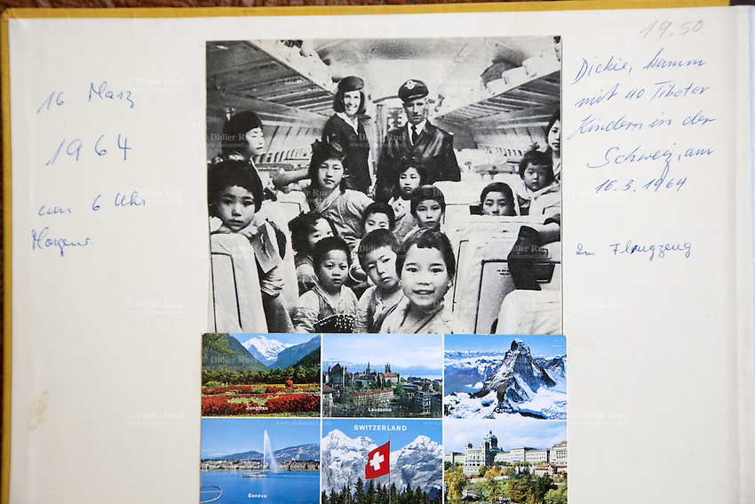 Switzerland. Canton Thurgau. Littenheid. Dicki Shitsetsang at home with the photo album of her arrival on board a Swissair flight in Zürich-Kloten airport on march 16, 1964. The elderly swiss tibetan woman is an Aeschimann's child who arrived 50 years ago in Switzerland to receive custody on a private initiative by an influential Swiss industrialist, Charles Aeschimann. In 1962, Charles Aeschimann agreed with the Dalai Lama to take 200 children and place them in Swiss foster homes and give them a chance for a better life and a good education. Most of the children still had parents in exile or in Tibet, just a few were orphans. A colorful postcard with swiss tourist symbols, Jungfrau, Lausanne, Matterhorn, Geneva and its water fountain, the swiss flag and the Alps, and the capital city Bern. 26.02.2015 © 2015 Didier Ruef