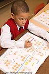 K-8 Parochial School Bronx New York Kindergarten boy sitting at desk working in math workbook vertical